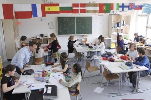 imagen de un aula digital con alumnos usando ordenadores.