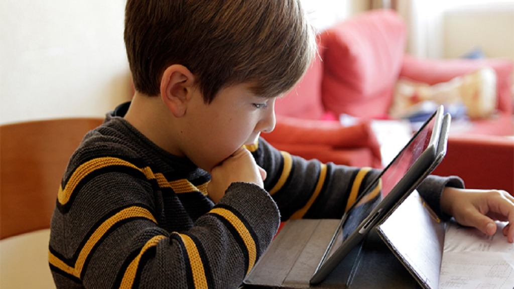 imagen de un niño mirando atentamente su tableta.