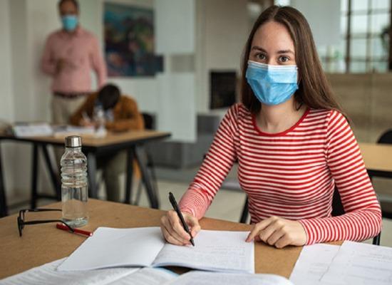 imagen de una estudiante frente a sus tareas.