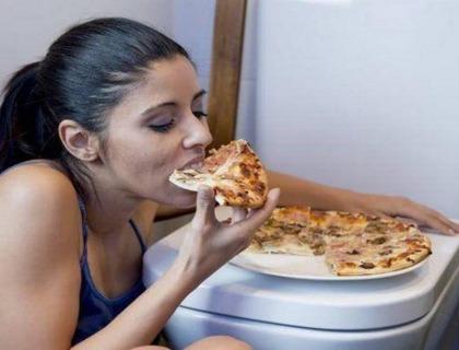 imagen de una joven comiendo en el cuarto de baño preparándose para vomitar lo comido.