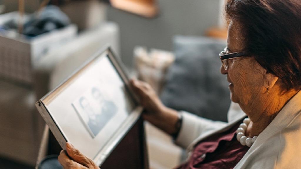 covid-19: imagen de un anciana mirando una foto de su marido fallecido.