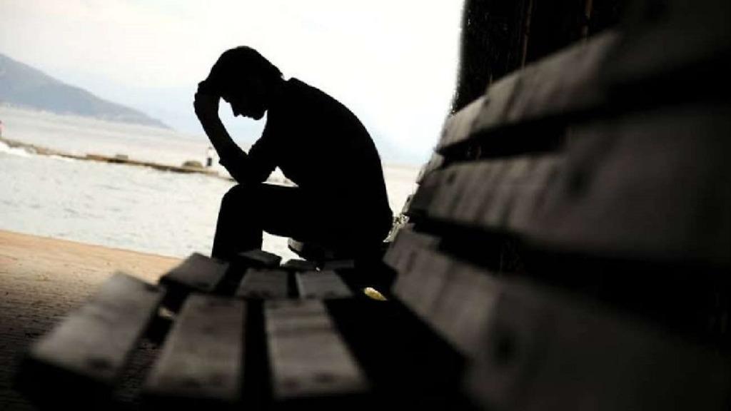 imagen de un hombre sentado en un banco con pensamientos suicidas.