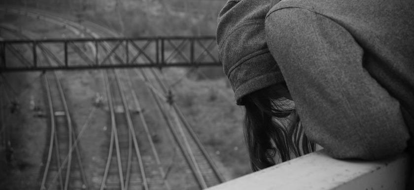 prevenir el suicidio: imagen de una joven sobre las vías del tren