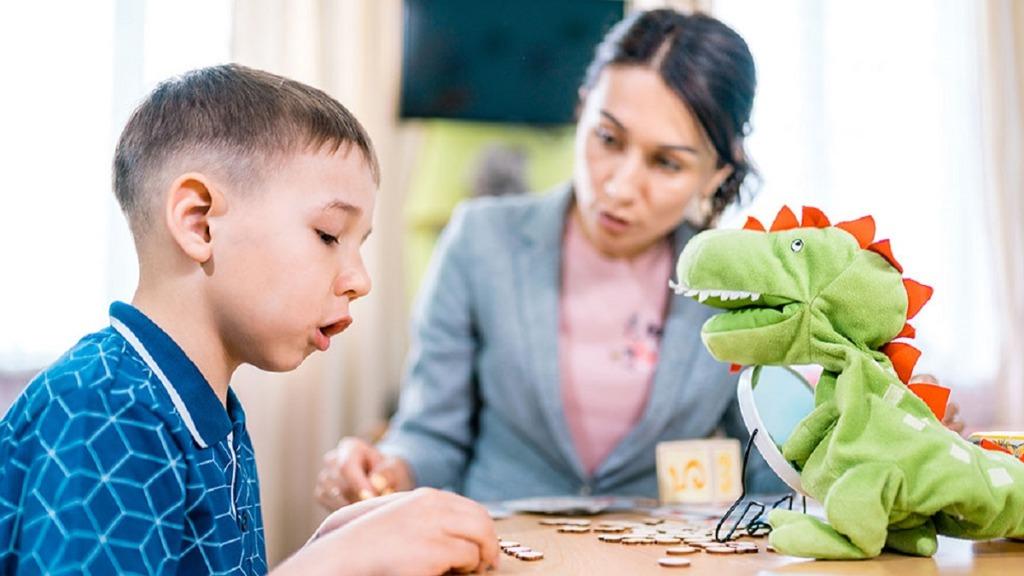 imagen de una profesora ayudando a un niño con tartamudez.