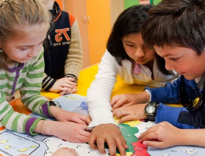 niños con discapacidad visual estudiando sobre un mapa en relieve.