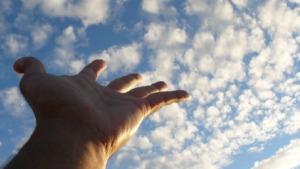 el arte de vivir, imagen de una mano tocando las nubes