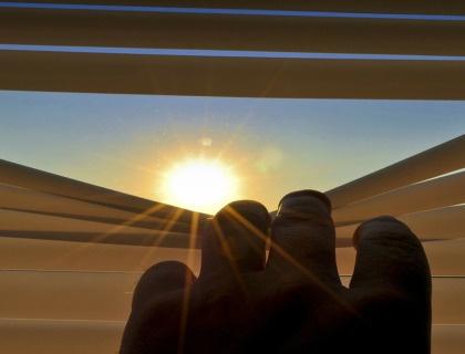 Vivir el Covid a ciegas. Imagen de una mano deslizando una cortina hacia abajo dejando entrar el sol
