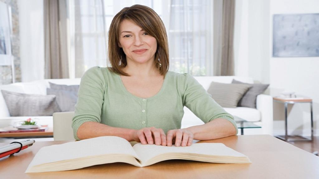 imagen de una mujer ciega leyendo braille