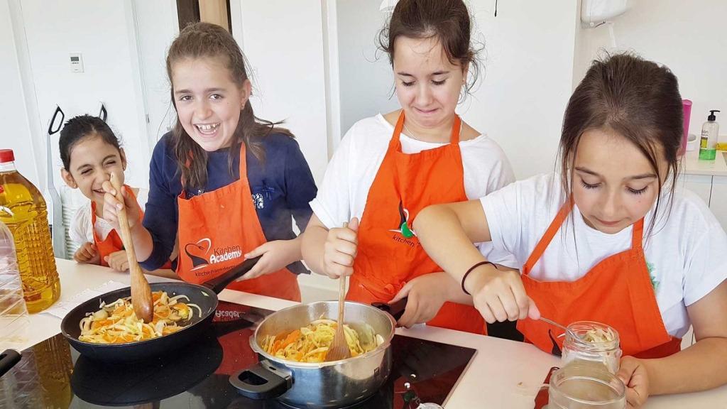 incorporar la cocina a las aulas: imagen de unos niños durante una clase de cocina