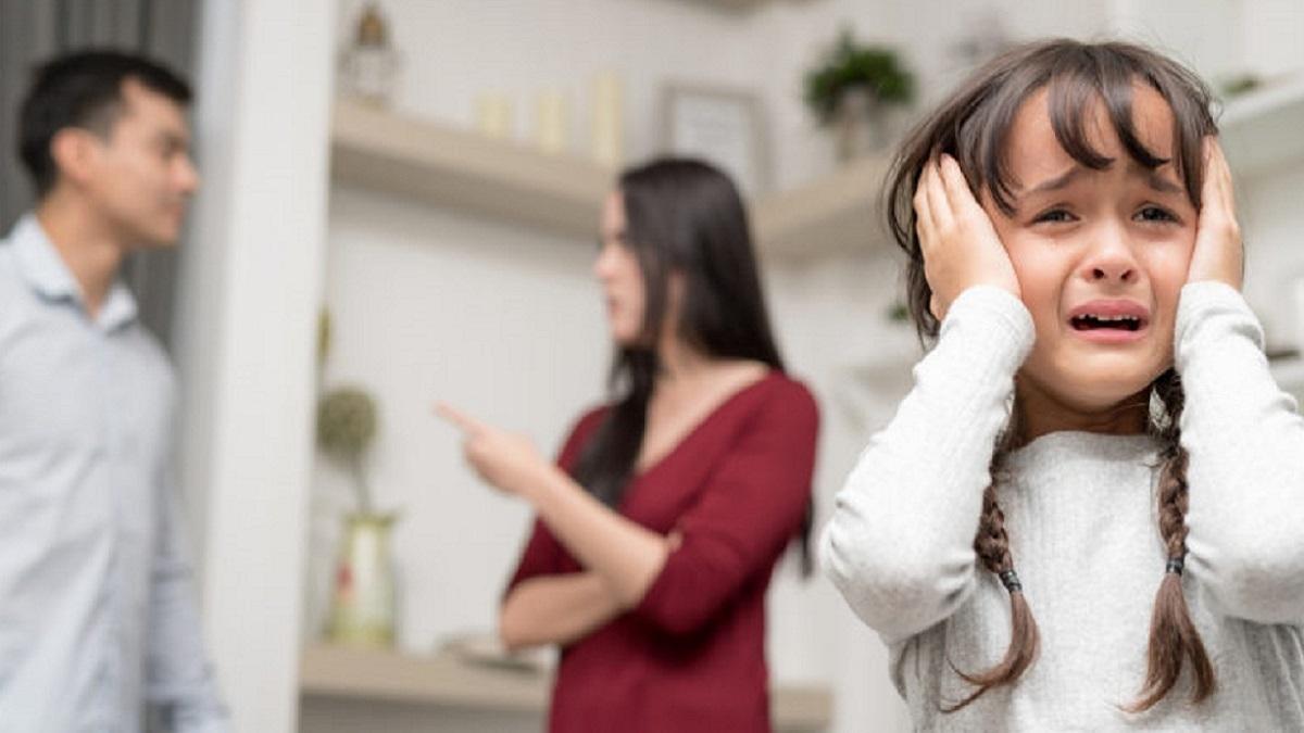violencia doméstica: imagen en primer plano de una niña tapándose los oídos para no oír la discusión de sus padres detrás de ella