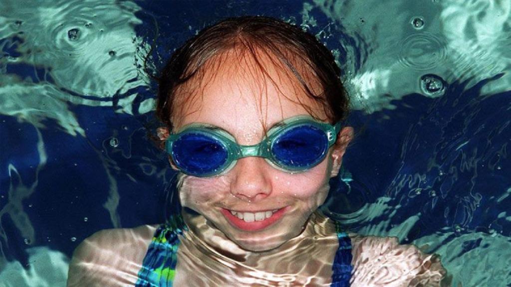gafas para nadar: imagen de una niña en la piscina llevando gafas
