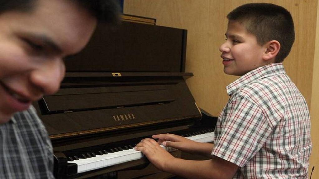 personas ciegas y formación musical: imagen de un niño ciego tocando el piano