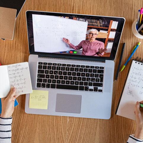 imagen de una videoconferencia con un profesor en la pantalla del portátil.