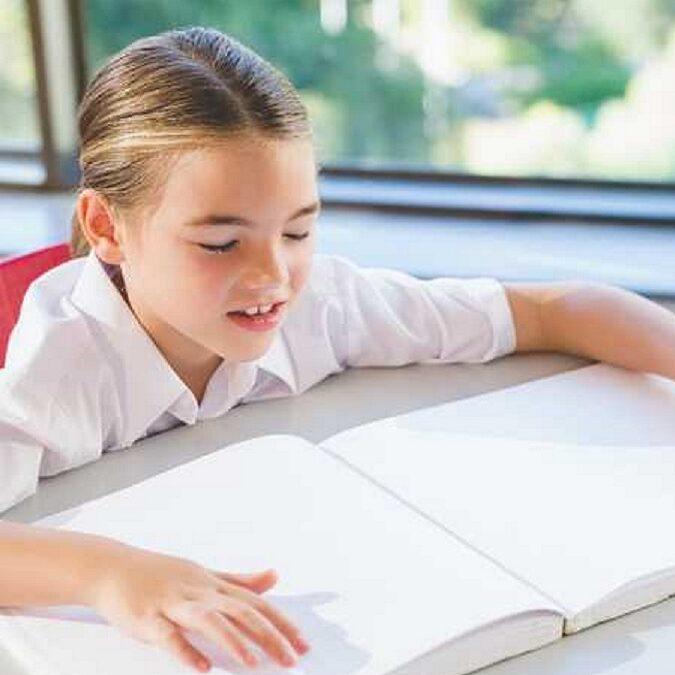 imagen de un niña leyendo un libro en braille