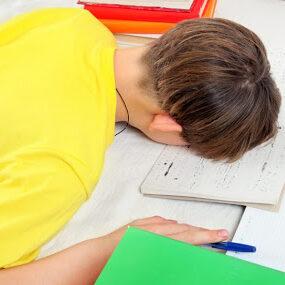 imagen de un niño agotado haciendo deberes.