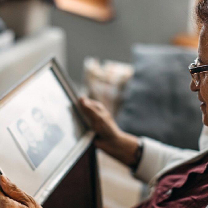 imagen de un anciana mirando una foto de su marido fallecido.