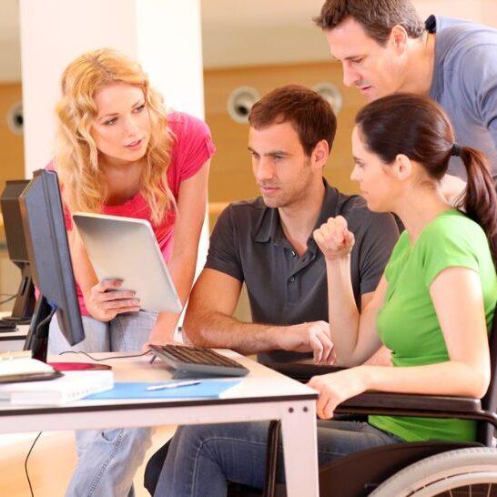 imagen de alumnos universitarios trabajando en equipo con una persona discapacitada.