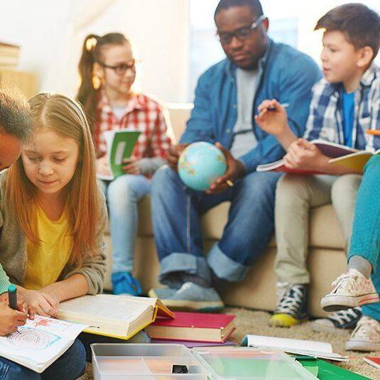 imagen de un profesor rodeado de sus alumnos.