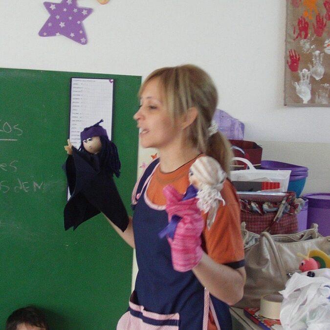 imagen de una profesora usando títeres para dar una clase.